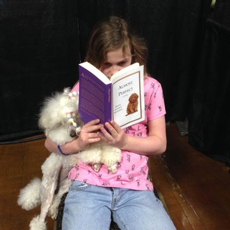 A girl and her dog relax with a good book